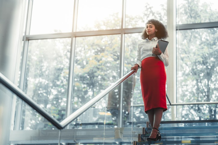 A municipal administrator in a red skirt stands on a staircase. Benefit administrators like her should seek out competitive quotes for stop-loss insurance each year.