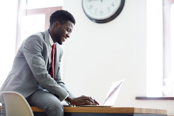 A young professional sits on a desk smiling and working on a laptop. Send-funded plans can be designed to appeal to prospective employees.