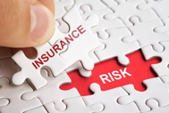 Self-funded insurance can be financially risky, but stop-loss coverage limits your liability. Puzzle pieces with insurance fits into risk space.